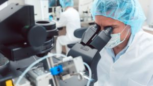 A scientist in medical gear peers through a microscope.