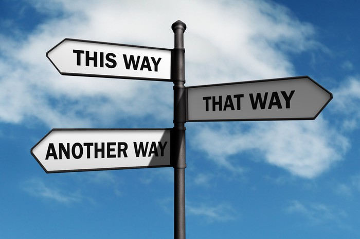 """A street sign with arrows pointing in different directions reads """"This Way,"""" """"That Way,"""" and """"Another Way."""""""