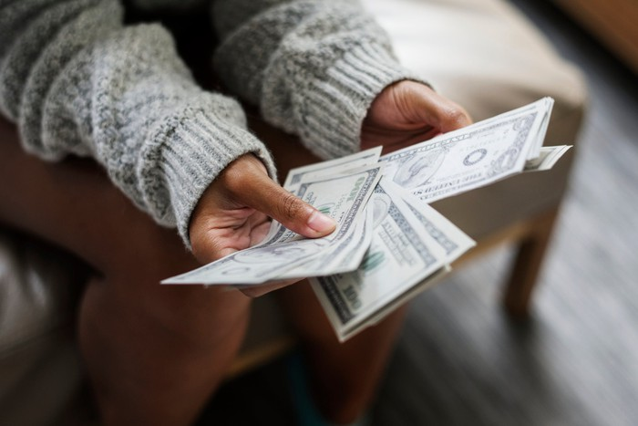 A woman's hands hold a set of fanned out of dollar bills.